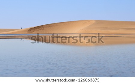Lone man walking in the dune and water landscape at the wetlands outside of Walvis Bay, Namibia. - stock photo