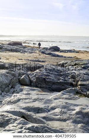 lone man walking on the rocks at ballybunion beach in ireland - stock photo