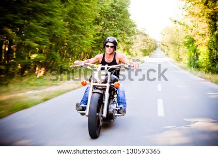 Lone Motorbike Rider In The Countryside - stock photo