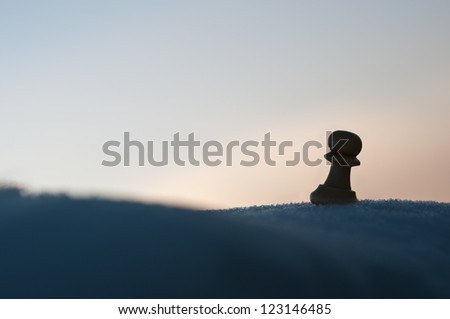 lone pawn in the snow horizon background - stock photo