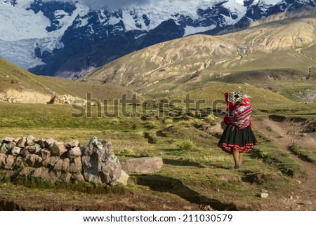 Lone peruvian woman walking with child on her back in south american Andes - stock photo