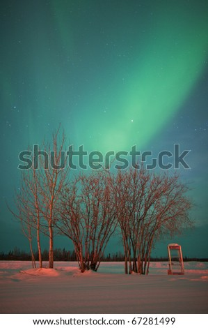 Lone phone booth stands in an open snow covered field under the northern lights. - stock photo