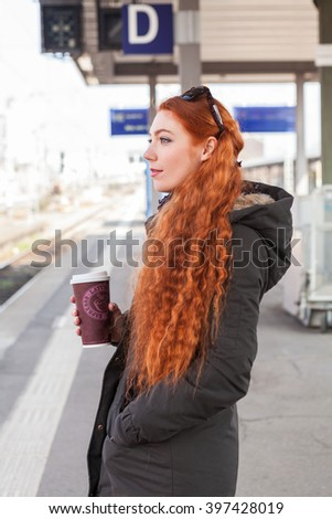Lone red headed commuter with sunglasses on her head holds a coffee cup while standing at train station waiting for her train - stock photo