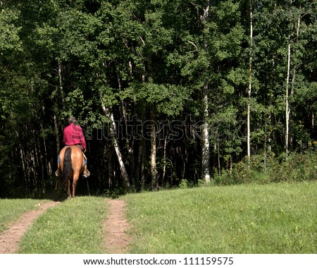 "Lone rider tops a hill and begins his journey into the woods... and the dark beyond.  Original Haiku: "" Over this hill my friend; Fear not what is beyond here; For you are Loved "" - stock photo"