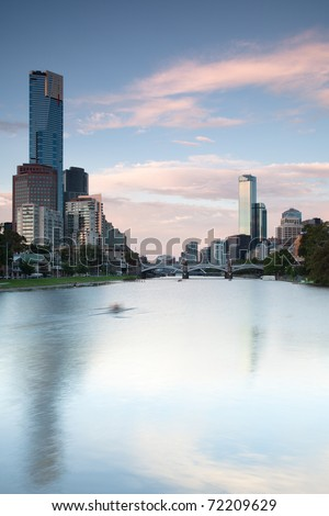 Lone rower on the Yarra River with the Melbourne skyline in the background - stock photo