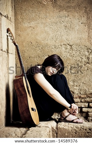 Lone sad guitarist sited in old brickwall. - stock photo