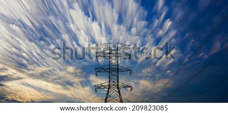 Lone silhouette of electrical pylon with clouds blended or stacked effect. - stock photo