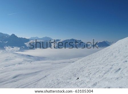 Lone skier in panoramic landscape of mountains. Skiing Les Contamines, French alps - stock photo