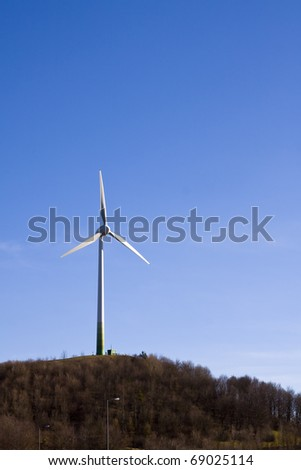 Lone standing wind turbine on a small wooded hill