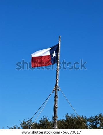 Lone star Texas flag flies proudly from a rustic wooden pole in the Fort Worth Stockyards tourist area. - stock photo