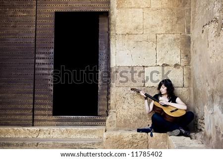 Lone street artist near old iron door. - stock photo