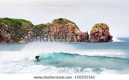 Lone surfer at Cape Woolamai in Australia. - stock photo
