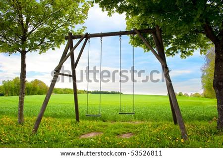 Lone swing seat in a summer field - stock photo