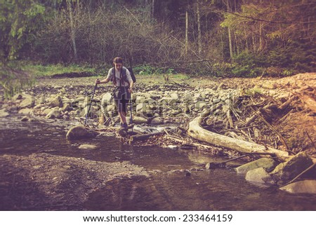 Lone traveler moving across the mountain river. Filtered image:cross processed vintage effect.  - stock photo