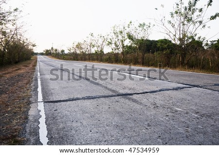 Lone tricycle in a long countryside road, Philippines - stock photo