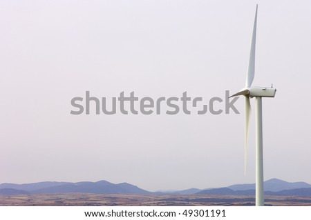 lone windmill with a white sky in a dry landscape