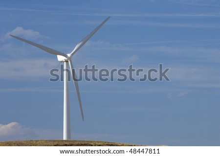 lone windmill with blue sky and clouds - stock photo