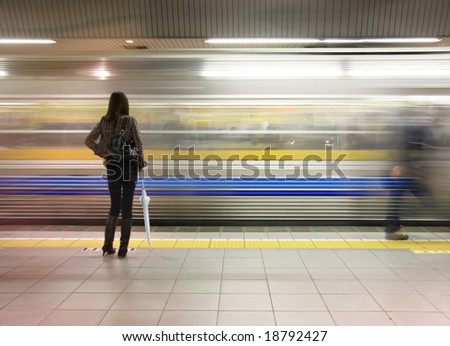 Lone woman watching subway speed by - stock photo