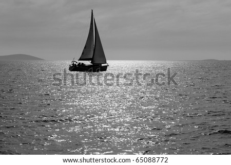 Lone yacht sailing in the Adriatic sea. Black and white image - stock photo