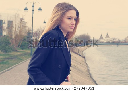 Loneliness. Blond haired women looking at river in city in loneliness. Instagram style color look. - stock photo