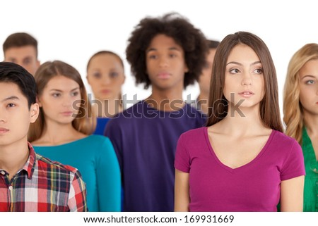 Loneliness in a crowd. Frustrated young woman standing among multi-ethnic group of people and looking away - stock photo