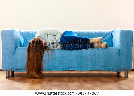 Loneliness negative emotion concept. Young sad stressed woman lying on couch at home - stock photo