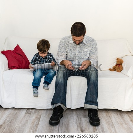 Loneliness of baby and father playing with tablet on a white sofa - stock photo