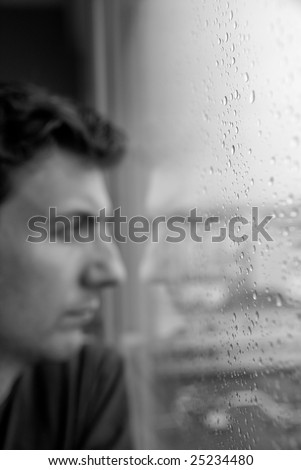 Loneliness or boredom, depression. Focus on the rain drops to leave the subject vaguely staring outside, with nothing to do. - stock photo