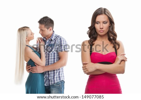 Loneliness. Young sad women standing with her arms crossed while another women and men hugging - stock photo