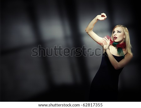 Lonely afraid blond lady in the dark interior with deep shadows. Artistic colors added - stock photo