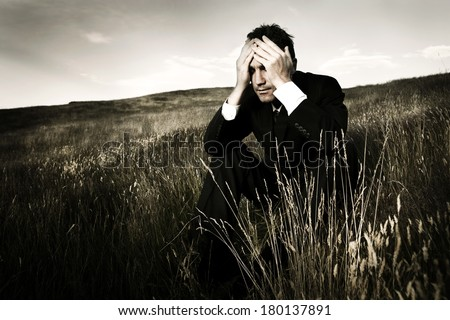 Lonely and Depressed Businessman On a Field - stock photo