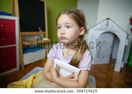 Lonely and sad little girl sitting on the floor, being blue and missing someone. Childhood, growing up, neglection, loneliness and sadness concept. 