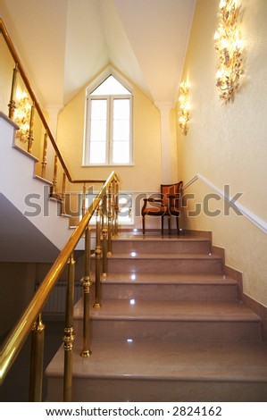 Lonely armchair on a ladder in beautiful hotel - stock photo