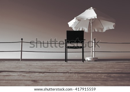 Lonely armchair on a wooden pier near the sea - stock photo