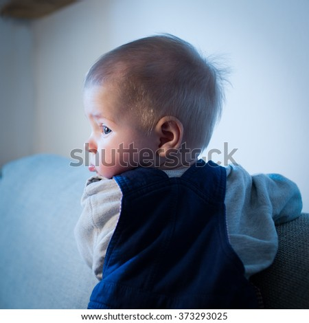 Lonely baby boy is standing on the couch in empty living room in the evening. Blue cold light from window. Color toned image. - stock photo