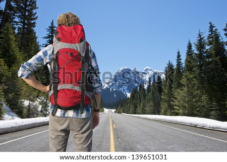 Lonely backpacker looking at the road ahead in beautiful mountain scenics, surrounded by large pine trees and the melting snow in the warm spring sun - stock photo