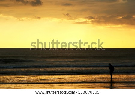 Lonely backpacker looking for sunset at Pacific coast, Nicaragua - stock photo