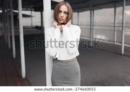 Lonely beautiful girl in a skirt and a sweater posing near water
