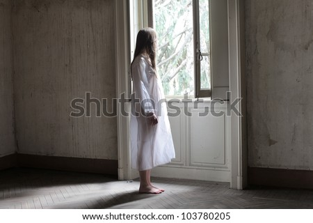 Lonely beautiful woman in night gown in an empty room - stock photo