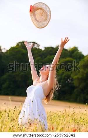 Lonely beautiful young blonde Scottish girl in white dress at golden wheat field catching her straw hat  - stock photo