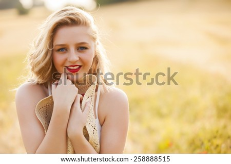 Lonely beautiful young blonde Scottish girl in white dress with straw hat posing at golden wheat field expressing calmness emotions - stock photo