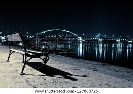 Lonely bench at the night. Selective focus on the wooden bench - stock photo