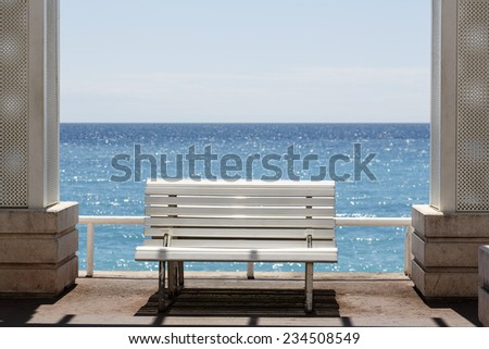 Lonely bench at the promenade on the shores of the Mediterranean - stock photo
