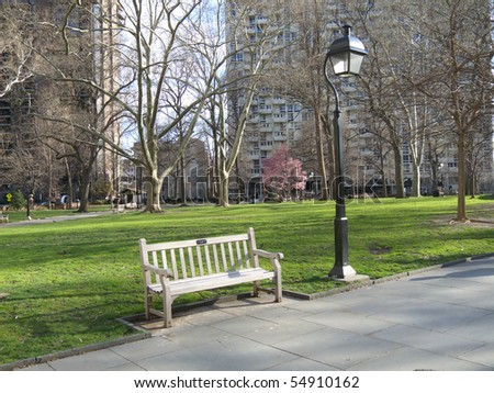 lonely bench in a park in springtime - stock photo