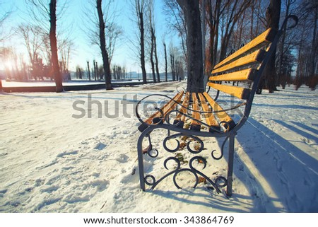 Lonely bench in city park. Winter time - stock photo