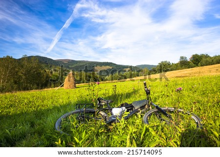 Lonely bicycle in mountain landscape. Green grass, blue sky  - stock photo
