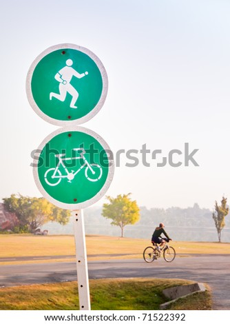 Lonely bicycle rider in the park with morning sunlight beside old traffic banner. - stock photo