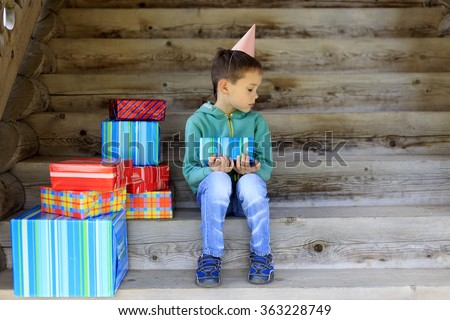 lonely birthday. one of the favorite and dear people did not come to the birthday to the little boy. child sits alone surrounded by gifts and sad looking an empty place next to him. - stock photo