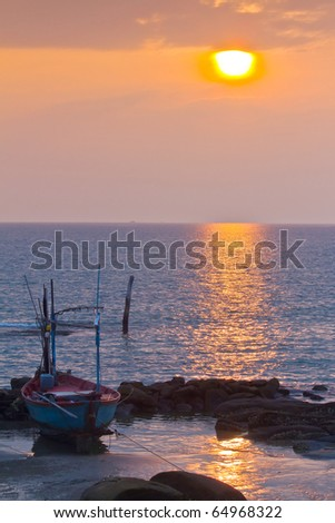 lonely boat during sunset over the sea, thailand - stock photo