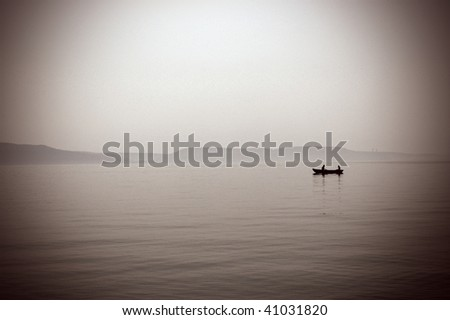 Lonely boat floating on the river - stock photo